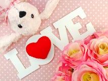 爱与玫瑰和逗人喜爱的玩偶情人节概念的词 免版税库存照片