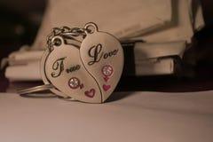 爱与题字的奖牌在两个一半`真实的`和`爱` 免版税库存照片