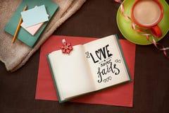 爱从未发生故障-在美好的葡萄酒背景的文本与咖啡和笔记本 库存照片