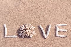 爱写由珊瑚在一个热带海滩 免版税库存图片