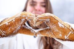 爱冬天 慈善 愉快的妇女显示心脏 在冬天手套心脏标志的妇女手塑造了生活方式和感觉 免版税图库摄影