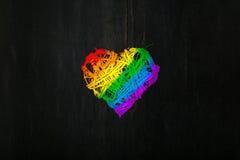 爱华伦泰在彩虹自豪感的心脏花圈上色黑暗的backg 免版税库存图片