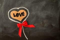 爱华伦泰心脏和红色弓在黑板 免版税库存图片