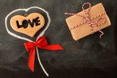 爱华伦泰心脏和红色弓在黑板 图库摄影
