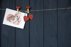 爱华伦泰` s卡片` Amore `自然绳子,并且垂悬在土气漂流木头纹理背景的红色别针,复制Sp 免版税图库摄影