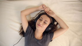 爱听的音乐的妇女在床上 股票视频