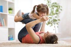 爱和家庭人概念-获得愉快的妈妈和儿童的女儿乐趣在家 库存照片