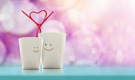 爱和情人节概念 有smi的愉快的恋人咖啡杯 免版税库存照片