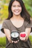 给爱和时间在华伦泰` s天 亚洲妇女手展示红色心脏和时钟 免版税库存照片