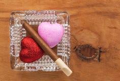 爱和有害的习性在一个玻璃烟灰缸 库存图片
