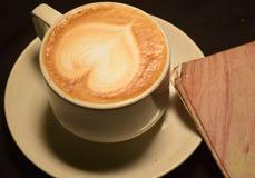 爱咖啡,拿铁艺术A杯子与心脏样式的在一个白色杯子 室内咖啡馆 免版税库存图片