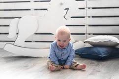 爱哭的人在地板上的男孩sittin 尖叫的婴孩哭泣和 图库摄影