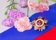 爱国战争的顺序与桃红色康乃馨的 图库摄影