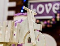 爱在一朵木背景、闪光灯和花的题字 特写镜头玩具自行车 库存图片