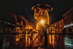 爱在亲吻的夫妇雨/剪影在伞下 免版税库存照片