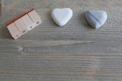 爱在唯一信件和两石头般的心在木背景的 免版税库存照片