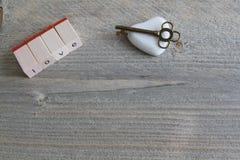 爱在唯一信件和石头般的心与钥匙的在木背景 免版税库存图片