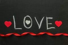 爱在有一条红色丝带的黑板写的文本 库存照片