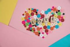 爱在木块写的词安置在五颜六色的按钮  免版税库存照片