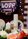 爱在木背景的题字,闪光灯,花 杉木蜡烛和分支  免版税图库摄影