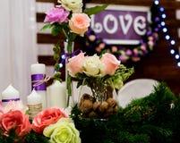 爱在木背景的题字,闪光灯,花 杉木蜡烛和分支  免版税库存图片