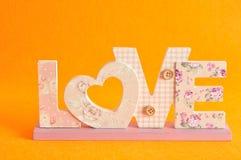 爱在橙色背景隔绝的桃红色信件 免版税库存图片