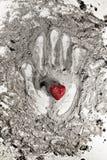 爱在灰的心脏在手边印刷品 免版税库存图片