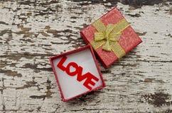 爱在礼物盒的字母表在难看的东西木头背景 免版税库存图片