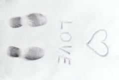 爱在雪写的心脏标志 免版税库存图片