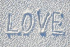 爱在雪写的文本为纹理或背景-寒假概念 晴天,与阴影的明亮的光,平的位置,上面 免版税图库摄影