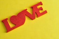 爱在黄色背景隔绝的红色信件 库存图片