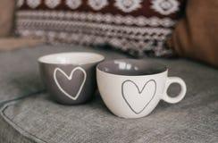 爱夫妇在家内部的两杯子心脏 图库摄影