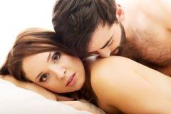 年轻爱夫妇在床上 库存图片