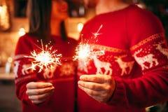 爱夫妇在手,圣诞节上拿着闪烁发光物 免版税库存图片