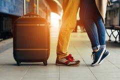 爱夫妇愉快拥抱在国家的火车站的腿在到来以后在秋天与温暖的阳光 免版税库存照片