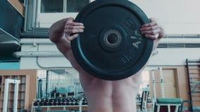 爱好健美者做与杠铃的转动的锻炼 股票录像
