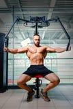 爱好健美者大厦胳膊在健身房背景干涉 有一臂之力肌肉的一位赤裸上身的运动员 坚硬锻炼概念 免版税库存照片