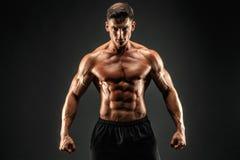 爱好健美者摆在 黑暗的背景的健身肌肉的人 库存图片