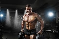 爱好健美者肌肉与重量的运动员训练在健身房 免版税库存照片