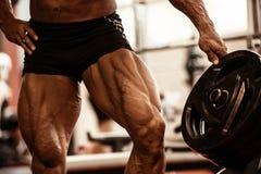 爱好健美者肌肉腿特写镜头  做在健身房的运动员人锻炼锻炼 免版税库存照片