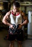 爱好健美者训练在健身房的肌肉 执行健身他的人反映培训水 免版税库存图片
