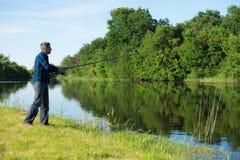 爱好渔夫在河岸钓鱼 免版税库存照片