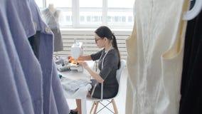 爱好缝合和一个小企业概念 年轻俏丽的妇女裁缝在缝纫机缝合 做服装的裁缝 股票视频
