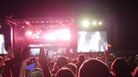 爱好者人记录录影并且拍在巧妙的电话的照片在音乐会党,手机在手中做照片 股票录像