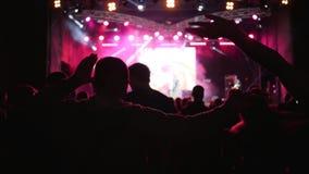 爱好者是在背景生动的舞蹈和挥动手被照亮阶段在音乐会在夜 股票录像