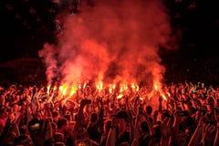 爱好者烧红色火光在摇滚乐音乐会 欢呼的音乐会人群 火显示 库存照片