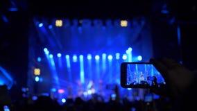 爱好者的胳膊与智能手机的做照片和录像在阶段泛光灯的摇滚乐音乐会在夜 影视素材