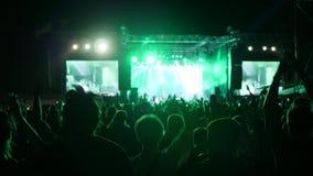 爱好者跳跃并且跳舞在音乐会,激动的在岩石节日的观众挥动的手,胳膊被举在明亮的光的人群 影视素材