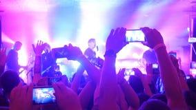 爱好者递录音录影和与巧妙的电话的采取图片在音乐音乐会 集会在摇滚乐音乐会的人人群 免版税图库摄影