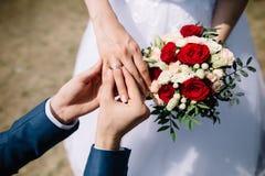 爱婚姻 外面艺术土气婚礼 修饰把金黄圆环放在新娘` s手指上 红色花束和 免版税库存照片
